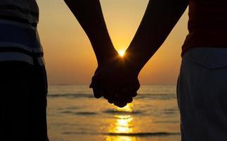paar hand in hand bij zonsondergang foto