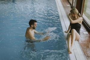jong koppel ontspannen aan het zwembad van het interieur zwembad