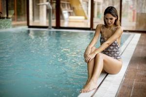 mooie jonge vrouw zit bij het zwembad foto