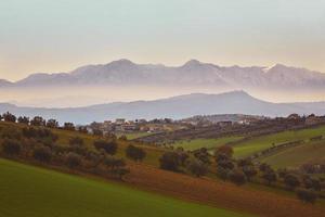 panorama van het Italiaanse platteland met mistige en besneeuwde bergen