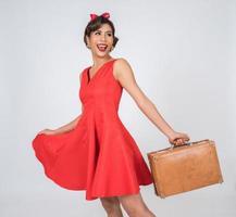 retro modieuze vrouw houdt bagage om te reizen foto