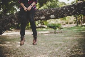 jonge wandelaar vrouw zittend op een boomtak