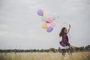 mooie jonge hipster vrouw met kleurrijke ballonnen buitenshuis