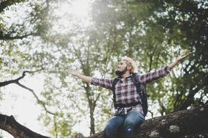 jonge wandelaar hipster man zittend op een boomtak met uitgestrekte armen