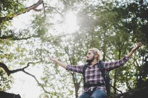 jonge hipster man zittend op een boomtak in het park.