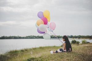 klein meisje spelen met ballonnen op weide veld