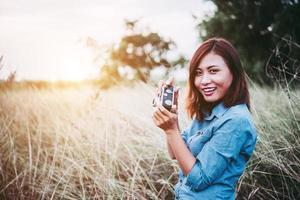 gelukkige jonge hipster vrouw met vintage camera in veld