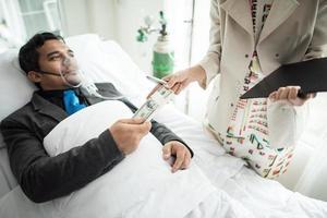 zakenman met zuurstofmasker werken vanuit bed geld overhandigen aan iemand