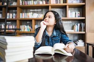 jonge vrouw leesboek binnen zitten in een stedelijk café foto
