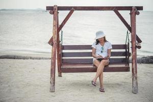 mooie vrouw op een schommel die op haar blocnote schrijft foto