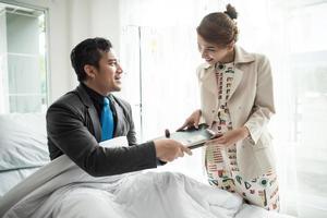 zakenman werken vanuit bed met zakenpartner