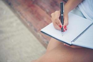 mooie jonge vrouw op een schommel die op haar blocnote schrijft foto