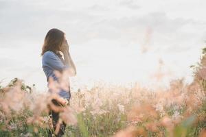 trieste vrouw stond in een veld met zonsondergang achtergrond foto