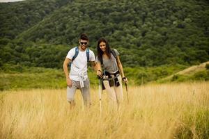 lachende paar wandelen met rugzakken over groene heuvels foto
