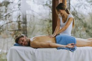 knappe jongeman liggend en met rugmassage in spa salon tijdens winterseizoen foto