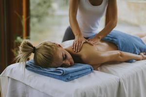 mooie jonge vrouw liggen en met rugmassage in spa salon tijdens winterseizoen foto