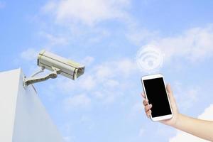 telefoon en beveiligingscamera bij het bouwen met blauwe hemel foto