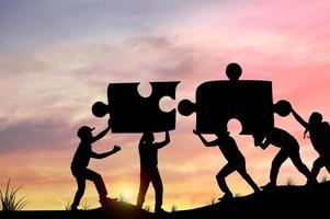 silhouet van mensen die puzzelstukjes helpen verbinden
