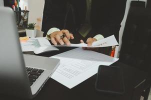 een zakenman die zakelijke documenten bekijkt en een pen met een computer, laptop en smartphone vasthoudt aan het bureau dat vanuit huis werkt