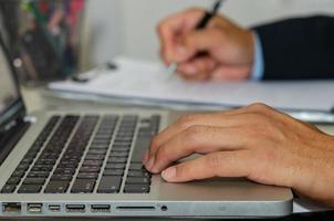 de hand van een zakenman op een computer en houdt een pen vast om zakelijke documenten op het bureau te schrijven