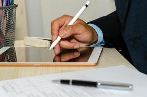 een zakenman met behulp van een tablet met zakelijke documenten en pennen aan de balie
