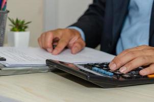 een zakenman die zakelijke documenten bekijkt en aan een rekenmachine werkt die vanuit huis werkt