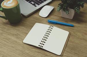 een blanco notebook liggend op een houten tafel en een groene koffiemok op de computer