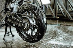 een motorfiets wassen in de autowaswinkel foto