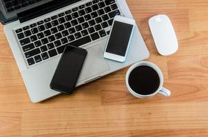 een laptop en smartphones op een oud houten bureau