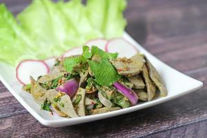 gesneden varkenslever pittige salade met slablaadjes in witte schotel op houten tafel