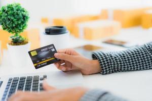 vrouw met behulp van creditcard met laptop voor online winkelen