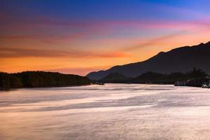 zonsondergang over water en bergen foto