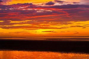 levendige zonsondergang over water foto