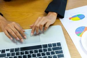 persoon die op een laptop op een bureau werkt foto