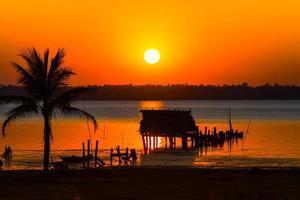 silhouet van een hut tegen een kleurrijke zonsondergang