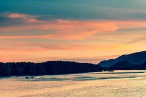 zonsondergang over een oceaan met bergen