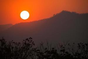 oranje zonsondergang over bergen foto