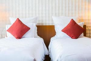 twee aparte bedden met rode kussens