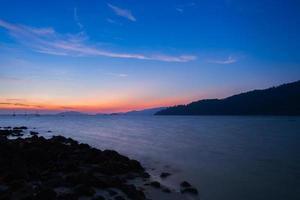 kleurrijke zonsondergang over de oceaan met bergen foto