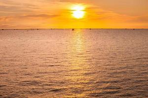 een oranje zonsondergang boven een watermassa foto