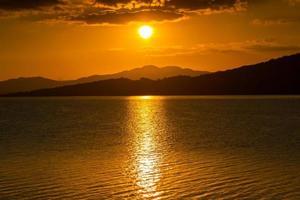 oranje zonsondergang over de oceaan en de bergen foto