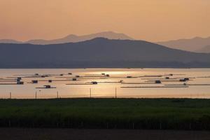 drijvende houten hutten op water bij zonsondergang
