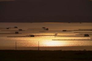 drijvende hutten op het water bij zonsondergang