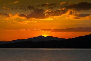 ondergaande zon achter bergen foto