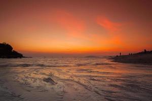 oranje zonsondergang over water op een strand foto