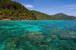 blauwe zee met groene bergen foto