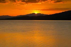 levendige oranje zonsondergang over bergen en de oceaan foto