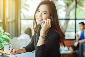 Aziatische zaken vrouw praten over de telefoon foto