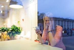 vrouw in een café met behulp van een telefoon foto
