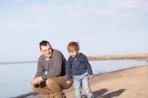 vader met zijn jonge zoon op het strand foto